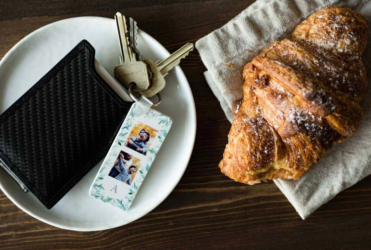 Photo keychain and wallet on a table with a croissant.